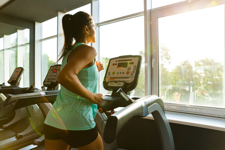Side view of Young concentrated sports woman running on treadmill near the window in gym