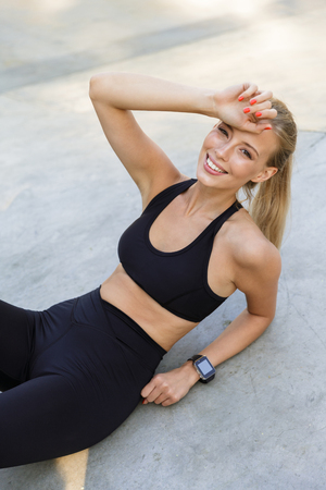 Image of happy beautiful young sports woman outdoors lies have a rest. Stok Fotoğraf