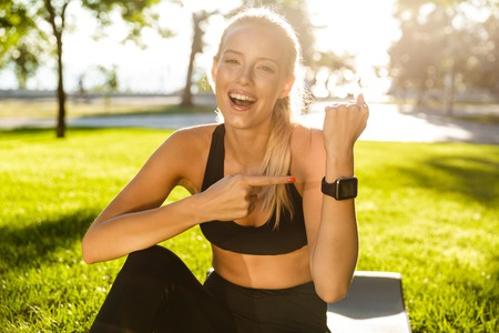 Image of cute cheerful young sports woman outdoors sitting on grass showing watch clock.