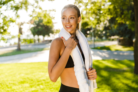 Image of pretty beautiful young sports woman outdoors on grass looking aside holding towel.