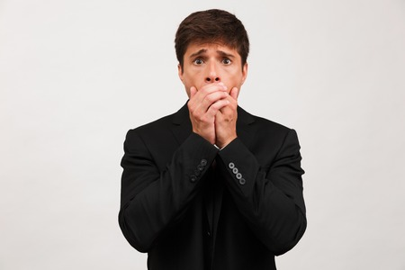 Image of scared young businessman standing isolated over white background wall covering mouth. Stock Photo - 110088048