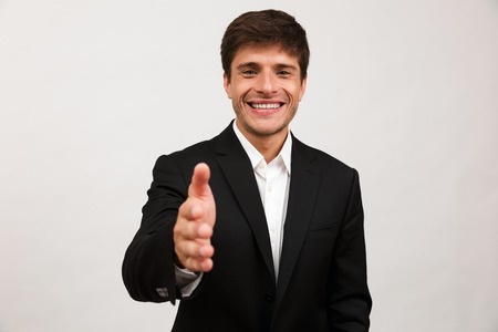 Image of handsome cheerful young businessman standing isolated over white background wall give a hand to you for handshake.