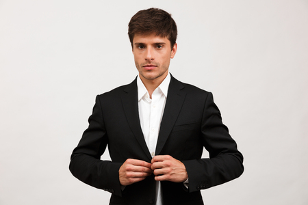 Image of handsome serious young businessman standing isolated over white background wall.