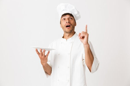 Image of shocked handsome young chef man standing isolated over white wall background pointing to copyspace holding plate. 版權商用圖片