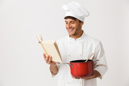 Image of handsome young chef man isolated over white wall background cooking reading book.