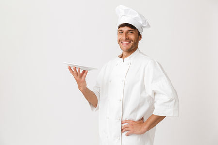 Image of cheerful handsome young chef man standing isolated over white wall background holding plate. Stock fotó