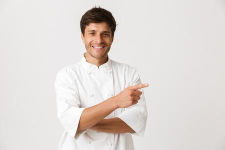 Bild des hübschen jungen Kochmannes, der lokalisiert über weißem Wandhintergrund steht und auf Exemplar zeigt.