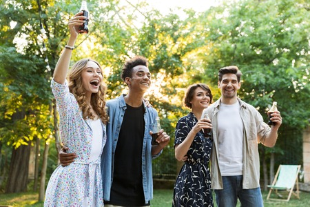 Photo of happy excited emotional young friends outdoors in park having fun walking drinking soda.