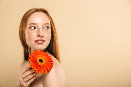 Photo of young redhead woman standing over beige background wall looking aside holding flower.