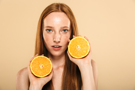 Photo of young redhead woman standing isolated over beige background wall holding orange.