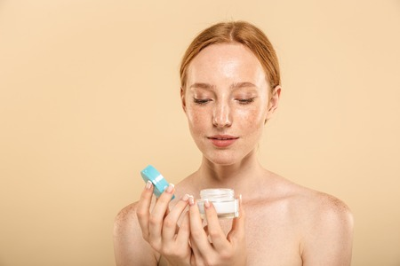 Beauty portrait of a sensual young redhead girl with freckles isolated over beige background, applying facial cream from a container