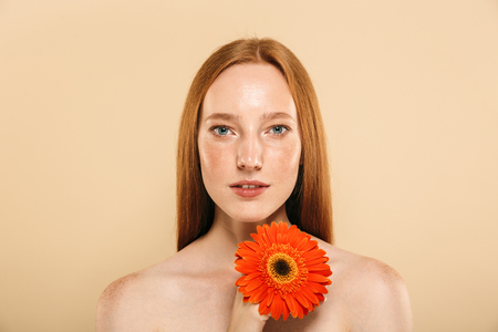 Photo of cute gorgeous young redhead woman standing over beige background wall looking camera holding flower.