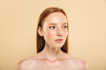 Beauty portrait of a young topless redhead girl with freckles isolated over beige background, looking away Stock Photo