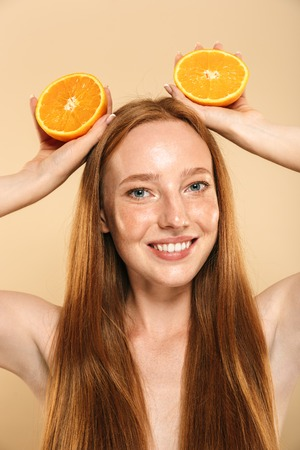 Photo of young smiling redhead woman standing isolated over beige background wall holding orange. Looking camera.