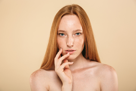 Beauty portrait of a sensual young topless redhead girl with freckles isolated over beige background
