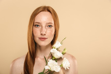 Beauty portrait of a smiling young topless redhead girl with freckles isolated over beige background, posing with eustoma flowers