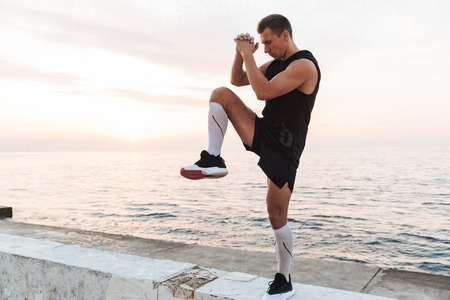Image of handsome strong young sportsman outdoors at the beach make stretching exercises.