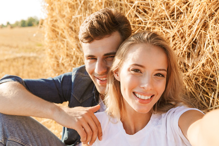 Photo of beautiful couple man and woman taking selfie while sitting under big haystack in golden field during sunny day