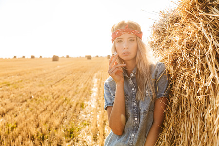 Image of stylish woman 20s standing near big haystack in golden field and smoking cigarette during sunny day 写真素材