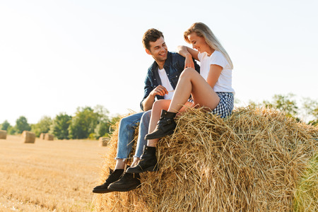 Portrait of happy man and woman sitting on big haystack in golden field during sunny day