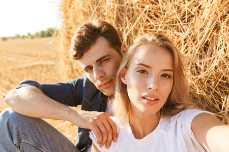 Photo of young couple man and woman taking selfie while sitting under big haystack in golden field during sunny day