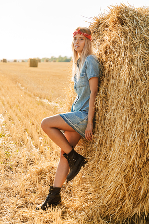 Full length image of gorgeous woman 20s standing near big haystack in golden field and smoking cigarette during sunny day