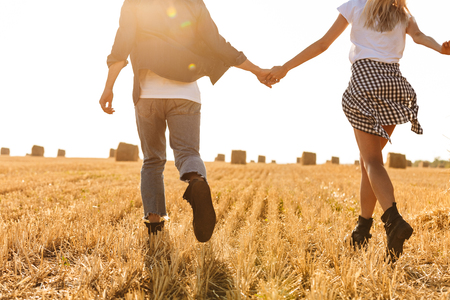 Cropped photo of young man and woman running through golden field with bunch of haystacks during sunny day Foto de archivo