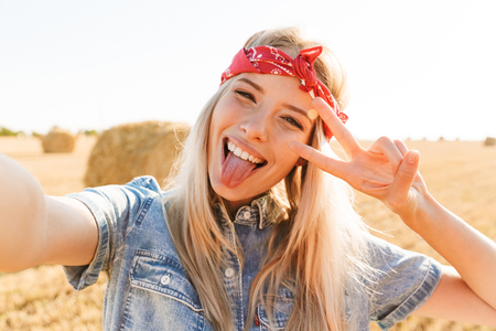 Beautiful smiling young blonde girl in headband at the wheat field, taking a selfie, sticking her tongue out Stockfoto