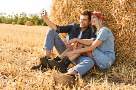 Photo of young couple man and woman smiling while sitting under big haystack in golden field during sunny day