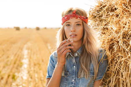 Image of gorgeous woman 20s standing near big haystack in golden field and smoking cigarette during sunny day