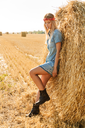 Immagine a tutta lunghezza di una donna adorabile di 20 anni in piedi vicino a un grande mucchio di fieno in un campo dorato e che fuma sigarette durante la giornata di sole Archivio Fotografico