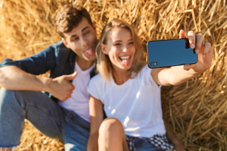 Photo of amazing couple man and woman taking selfie while sitting under big haystack in golden field during sunny day
