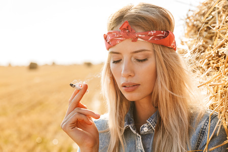 Image of beautiful woman 20s standing near big haystack in golden field and smoking cigarette during sunny day