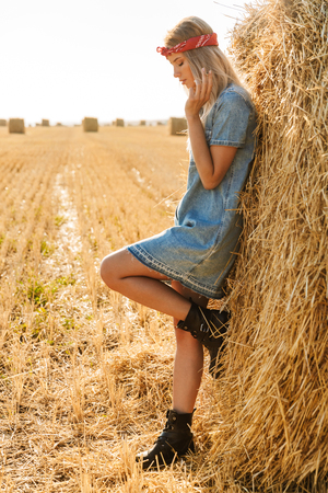 Full length image of sexual woman 20s standing near big haystack in golden field and smoking cigarette during sunny day 写真素材