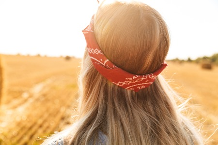 Back view of a young blonde girl in headband at the wheat field looking away