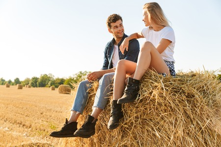 Smiling young couple sitting together on a haystack at the field, talking