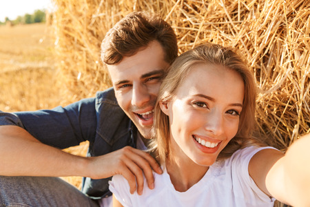 Photo of smiling couple man and woman taking selfie while sitting under big haystack in golden field during sunny day 写真素材