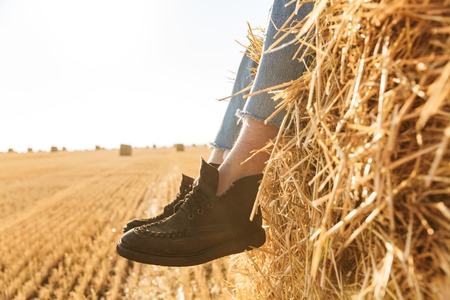 Close up of men's feet in shoes on a haystack at the wheat field Zdjęcie Seryjne