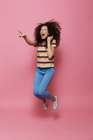 Full length photo of excited woman 20s with curly hair jumping and pointing finger aside isolated over pink background Stock Photo