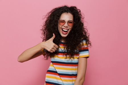 Image of happy cute young woman posing isolated over pink background make thumbs up gesture.