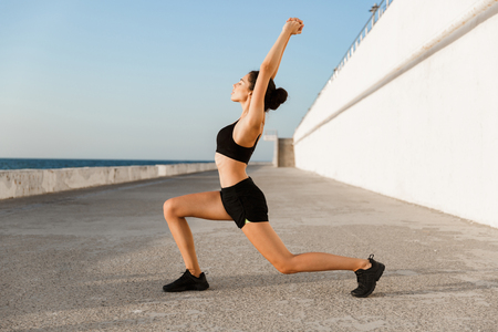 Confident young sportswoman outdoors at the seaside, doing lunges