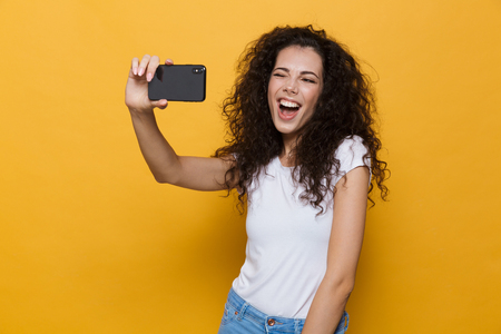 Image of an excited happy cute young woman posing isolated over yellow background take a selfie by mobile phone.