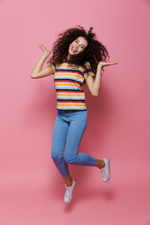 Full length photo of cute woman 20s with curly hair having fun and jumping isolated over pink background