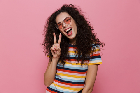 Image of happy cute young woman posing isolated over pink background make peace gesture. Banco de Imagens