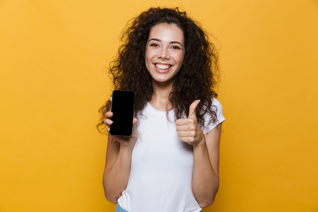 Image of an excited happy cute young woman posing isolated over yellow background showing display of mobile phone make thumbs up.