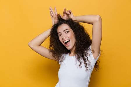 Image of a funny cute young woman posing isolated over yellow background.