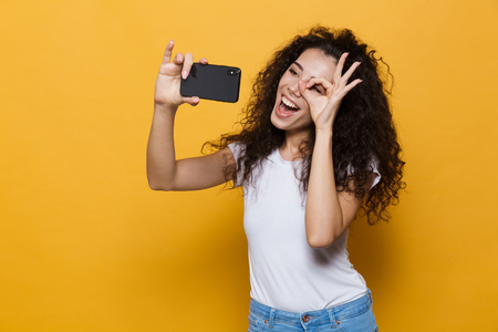 Image of an excited happy cute young woman posing isolated over yellow background take a selfie by mobile phone showing ok gesture.