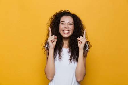 Image of happy excited young cute woman posing isolated over yellow background pointing. Banco de Imagens