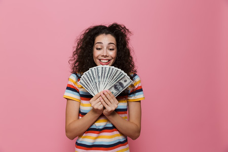 Image of brunette woman 20s with curly hair holding fan of dollar money isolated over pink background