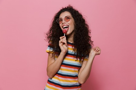 Image of an excited happy cute young woman posing isolated over pink background eat candy lollipop. Banco de Imagens - 110913984